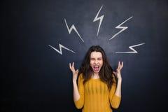 Wütende Frau, die über gezogenen Hochspannungszeichen auf Tafel schreit Stockfotografie