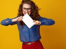 Wütende modische Frau gegen beißenden Tablet-PC des gelben Hintergrundes Stockbild