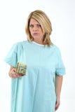 Wütender blonder Frauenpatient im Krankenhauskleid Stockbild