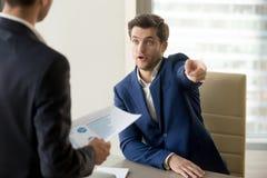 Wütender Chef, der den inkompetenten Angestellten, unzufrieden gemacht mit Schlechtem feuert lizenzfreies stockfoto