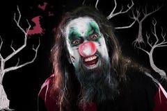 Wütender Clown, der vor schwarzem Hintergrund mit Bäumen und b lacht Lizenzfreie Stockfotografie