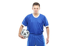 Wütender Fußballspieler, der einen Fußball anhält Stockbild
