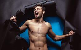 Wütender junger Mann, der oben den Hintergrund zerreißt Stockfotografie