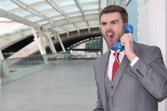 Wütender Mann, der durch alte Schulmünztelefon nennt Lizenzfreies Stockfoto