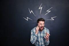 Wütender Mann, der Handy verwendet und über Tafelhintergrund schreit Stockfotografie