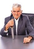 Wütender Senior mit einem Messer, das Kamera betrachtet Lizenzfreie Stockfotografie