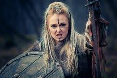 Wütender wütender Wikinger-Frauenkrieger im Angriff Sward und Schild Gl?ckliches junges M?dchen, das Taschen auf einem wei?en Hin lizenzfreies stockfoto