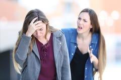 Wütendes Mädchen, das ihren beteiligten Freund schilt stockbild
