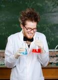 Wütendes Professorlachen, das zwei Flaschen hält Lizenzfreies Stockfoto
