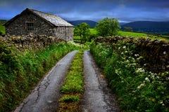 Wąska droga, kamieni ogrodzenia i stary kamienia dom w Yorkshire, zdjęcie stock