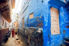 Wąska indyjska ulica z błękitów domami i gnanie indyjska kobieta w India Zdjęcie Royalty Free