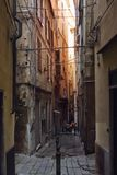 Wąska stara i ciemna ulica w genui Włochy zdjęcie stock