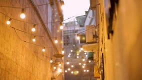 Wąska ulica iluminująca z żarówkami, świąteczny nastrój w nocy mieście, projekt zbiory wideo