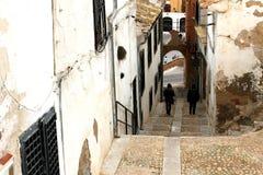 Wąska ulica w Villena mieście z długimi schodkami zestrzela przy odległością i dwa ludzie zdjęcia royalty free