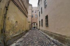 Wąska ulica z ścieżką brukowi kamienie Przejście między starymi dziejowymi wieżowami w Lviv, Ukraina zdjęcia stock