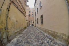 Wąska ulica z ścieżką brukowi kamienie Przejście między starymi dziejowymi wieżowami w Lviv, Ukraina zdjęcie stock