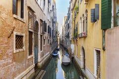 Wąski Wenecki kanał między kolorowymi domami z łodziami Obraz Stock