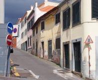 Wąskiej zaciszności pusta ulica w Funchal Madeira z starymi malującymi domami na stromym wzgórzu z żaluzjami i drogowymi znakami fotografia royalty free