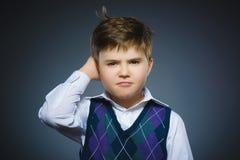 Wątpliwość, wyrażenie i ludzie pojęć, - chłopiec myśleć nad szarym tłem obrazy stock