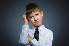 Wątpliwość, wyrażenie i ludzie pojęć, - chłopiec myśleć nad szarym tłem obraz royalty free