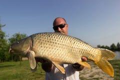 Wędkarz z karpiowym połowu trofeum karpiem i rybakiem, Karpiowy połowu trofeum Zdjęcie Royalty Free