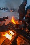 Wędrownicy ogrzewają nad ogieniem w zimnej pogodzie i śniegu fotografia stock