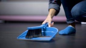Wędrowny żeński pracownik odkurza podłoga z muśnięciem, niedopłacony zatrudnienie obraz stock