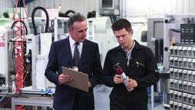 Właściciel biznesu w fabrycznym dyskutuje składniku z inżynierem zbiory