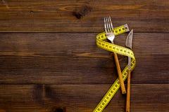 Właściwy odżywianie dla odchudzać Rozwidlenie i nóż z zdyszaną pomiarową taśmą na ciemnej drewnianej tło odgórnego widoku kopii p zdjęcia stock