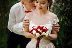Właśnie żonaty mężczyzna całuje jego narzeczony w zielonym parku fotografia stock