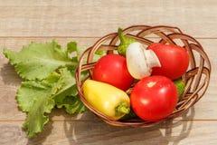 Właśnie ukradzeni pomidory i żółty dzwonkowy pieprz w łozinowym koszu w Obrazy Stock