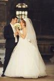 Właśnie zamężna kryjówka ich buziak za bukietem Zdjęcia Royalty Free