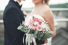 Właśnie zamężny ślub pary pozować i panny młodej mienie w ręka bukiecie fotografia stock