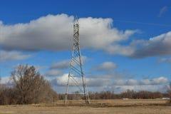 Władzy wierza w polu z niebieskiego nieba i bielu chmurami zdjęcia stock
