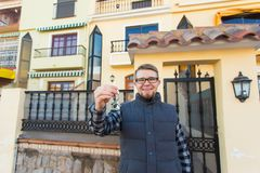 Własność, posiadanie, nowy dom i ludzie pojęć, - młody człowiek stoi na zewnątrz nowego domu z kluczami obrazy stock