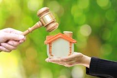 Własności aukcja, kobiety ręka mienia młoteczka dom na naturalnym zielonym tle, drewniany i wzorcowy, prawnik domowa nieruchomość zdjęcie royalty free