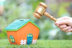 Własności aukcja, kobiety ręka mienia młoteczka dom na naturalnym zielonym tle, drewniany i wzorcowy, prawnik domowa nieruchomość zdjęcie stock