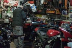 włochy Rzymu Grudzień 04, 2017: Mężczyzna pracuje w garażu naprawianiu Zdjęcie Stock