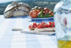 Włochy, Tuscany, Magliano, Bruschetta, chleb, pomidory i oliwa z oliwek na stole, obraz stock