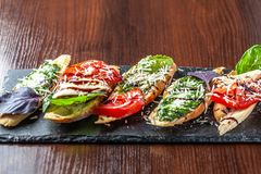 Włoscy bruschettes z mozzarella serem, pomidorami, pesto kumberlandem i parmesan serem na czarnym kamieniu na drewnianym stole, zdjęcie stock