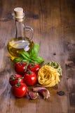 Włoscy i Śródziemnomorscy karmowi składniki na drewnianym tle Czereśniowi pomidory makarony, basilów liście i karafka z oliwa z o Fotografia Royalty Free