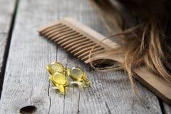 Włosiany nurishment witaminy serum kapsuła na drewnianym tle Obrazy Stock