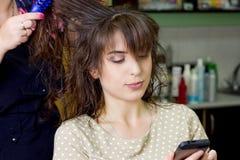Włosiany szczotkować proces Młoda dziewczyna gawędzi na telefonie obrazy stock