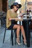 Włoska kobieta z kapeluszem i szkłami pisze wiadomości z smartphone obraz stock
