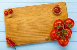 Włoska kuchnia, tnąca deska z pomidorami figlarki miejsca tex twój Zdjęcia Stock