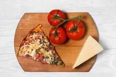 Włoska nieociosana pizza, strój jednoczęściowy na drewnianej tacy, biały drewniany stół z pomidorami i serem, fotografia stock