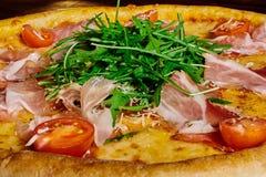 Włoska pizza z baleronem, pomidory i ziele na drewnianym stołowym ï ¿ ½, gubimy w górę fotografia stock