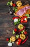 Włoski karmowy tło z mięsem, pomidory, spaghetti, czosnek, peppercorns, chili pieprz na drewno stole Obrazy Royalty Free