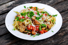 Włoski kurczak piersi spaghetti z czerwonym pieprzem, Parmezańskim serem i dzikimi rakietowymi życiami, na starym drewnianym stol Obraz Stock