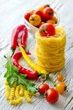 Włoski makaronu gniazdeczko z czereśniowymi pomidorami, chili i rucola, obraz stock